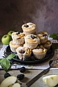 Blackberry and apple muffins stacked on a plate