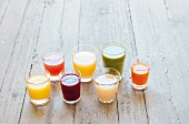 Seven different juices in glasses on a wooden surface