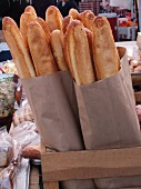 Baguettes in paper bags on a market stand