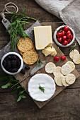 Käseplatte mit Sesam- und Weizencrackern, Kräutern, Kirschen und Brombeeren
