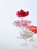 Red and white Christmas sweets in glass bowls