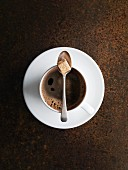 A cup of coffee with a spoon and sugar cube