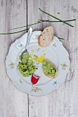 Avocado cream with chives and olive oil on a porcelain plate with a slice of baguette and radishes