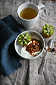 Breakfast tea, yoghurt muesli and kiwi