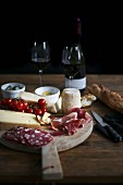 A wooden board with charcuterie, cheese, bread and red wine