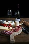 Holzteller mit Schinken, Wurst, Käse, Brot und Rotwein