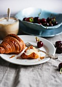 A croissant, cappuccino, cherries and strawberries