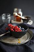 Fresh berries with honey in a dark bowl