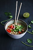 Asian noodle soup with lime, coriander and chopsticks