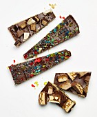 Broken chocolate decorated with chocolate bars and crushed bonbons