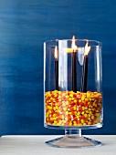 Halloweendekoration: Glasgefäss gefüllt mit Candy Corn als Windlicht für Kerzen