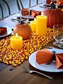Gedeckter Tisch für Halloween dekoriert mit Kürbissen, Kerzen und Candy Corn