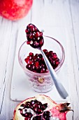 Pomegranate seeds in a glass and on a spoon