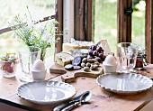 Frühstück mit weichen Eiern, Trauben, Marmelade, Salami, Käse und Caprese-Salat