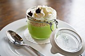 A creamy green dessert with biscuit crumbs, blackberry purée and whipped cream in a glass