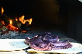 Unleavened bread and a whole octopus in a wood-fired oven