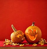 Zwei küssende Halloween-Kürbisse mit geschnitztem Frauen- und Männergesicht