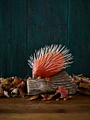 A hedgehog made from a pumpkin and toothpicks as Halloween decoration