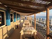 Sonnige Terrasse eines Strand-Restaurants