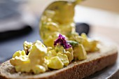 Egg salad with edible flowers on a slice of bread