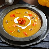 Pumpkin soup with cream and edible flowers