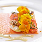 Smoked salmon with walnuts, shallots and yellow edible flowers