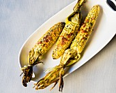 Grilled corn cobs with herbs, cheese and ham