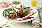 Lamb chops stuffed with pink peppercorns and pesto, served with asparagus and spring onions