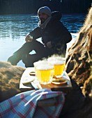 A man dressed in warm clothing sitting by the water with a glass of hot apple cider in his hand