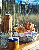 Hot dog buns, chutney and a flask on a table outside