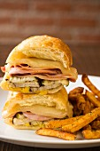 Warm ciabatta sandwiches with cheese, turkey ham, gherkins and chips