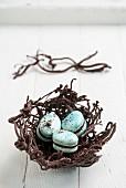 Drei blaue Macarons im Osternest