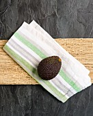 A whole avocado on a fabric napkin (seen from above)