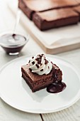 Chocolate tray bake cheesecake with cream and chocolate sauce