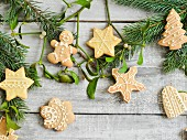 Gingerbread biscuits decorated with icing on a wooden surface with mistletoe and sprigs of pine