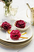 Place setting decorated with red roses and name tag for garden party