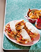 Prego rolls with chicken and cocktail tomatoes, served with potato wedges