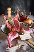 Rohes Kaninchen mit Kräutern und Gewürzen auf Holztisch