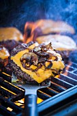 Cheeseburgers with fried onions on the barbecue