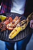 Grilled lobster and corn on the cob served on a barbecue griddle plate