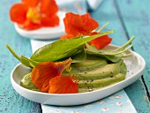 Spinach salad with avocado and nasturtium flowers