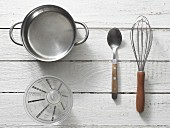 Kitchen utensils: a saucepan, measuring cup, spoon and whisk