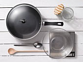 Assorted kitchen utensils:a frying pan, spoons, a preserving jar and scales