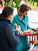 Frau serviert Pilzsuppe fürs Herbstbuffet im Freien