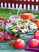 Pear and red cabbage salad with almonds on an autumnal table outside
