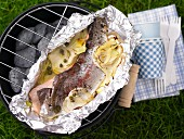 A trout fillet parcel on a charcoal barbecue