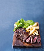 Grilled beef steak with chips on a wooden board