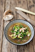 A bowl of Asian vegetable soup with Japanese buckwheat noodles on a wooden background