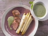 Oven-baked asparagus with pork fillet and basil sauce