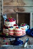 Kleine Naked Cakes mit frischen Beeren auf Tortenständer